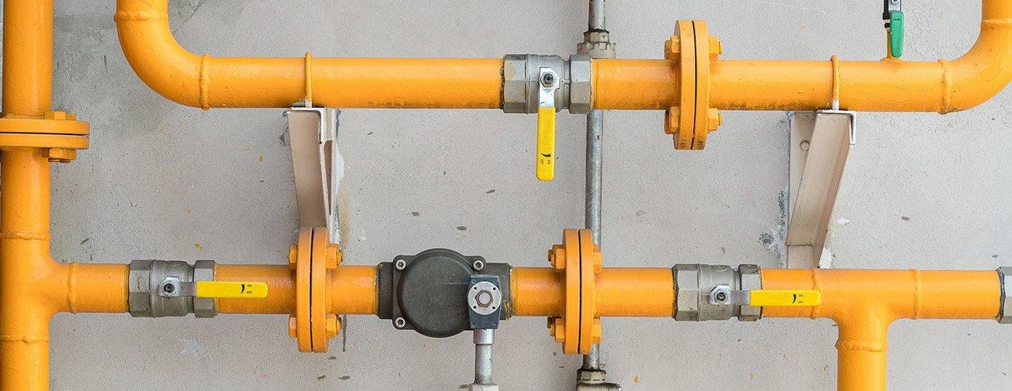 Gelbe Gasleitungen an der Wand montiert